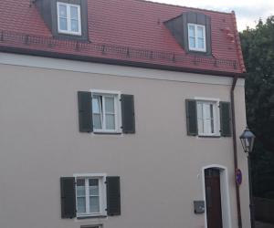 Cremefarbenes Haus mit dunkler Tür und Fensterläden und rotem Dach