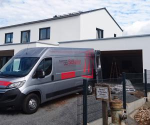 Transporter der Firma Schaller vor einem weißes Einfamilienhaus