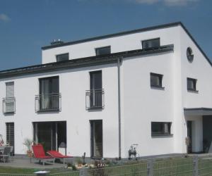 Weißes Einfamilienhaus mit Kunststofffenstern und großem Garten