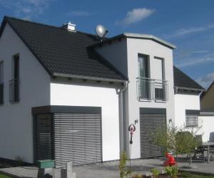 weißes Einfamilienhaus mit dunklem Dach und Raffstore-Blende