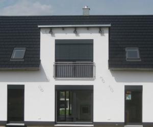 Weißes Einfamilienhaus mit dunklem Dach und dunklen Fensterrahmen