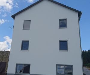 Hauswand eines weißes Familienhauses mit 6 Fenstern