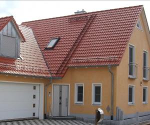 oranges Einfamilienhaus mit weißem Garagentor und Briefkasten