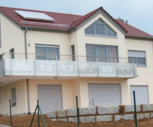 Cremefarbenes Einfamilienhaus mit Kunststoffrolladen mit sehr großen Balkon