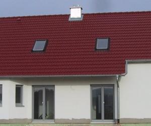 Seitenansicht eines weißen Hauses mit dunkelroten Dach