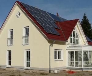 cremefarbenes Haus mit schmalen Fenster, Wintergarten und Solarzellen auf dem Dach