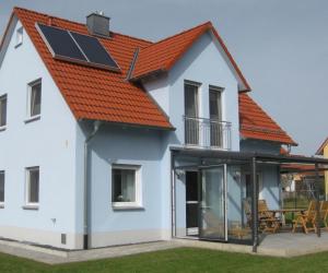 Hellblaues Haus mit rotem Dach und überdachter Terrasse