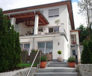 Treppen führen zu weißen Haus mit 3 Stockwerke und großem Balkon