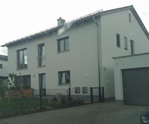 weißes Haus mit Garage und Garten